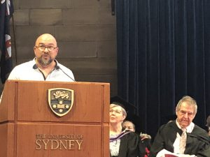 Photo of Scott Stephens giving the occasional address at the 2018 SCD graduation ceremony.